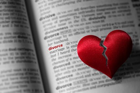 Red broken heart on dictionary divorce definition. The concept of divorce, parting, infidelity . Selective focus.