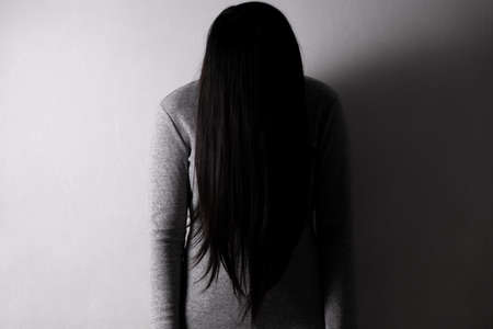 Darkness woman. Sad woman stand and cry alone in a empty room. Stock fotó