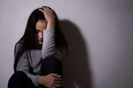 sad woman hug her knee and cry. Sad woman sitting alone in a empty room. Stockfoto