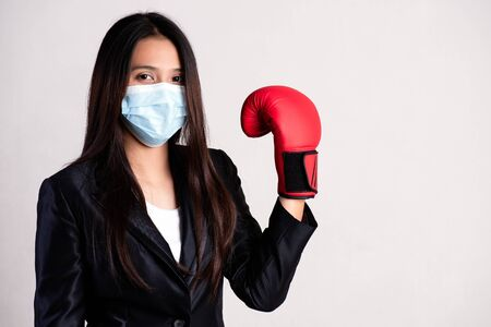 Close up of a businesswoman in a suit wearing red boxing gloves and Protective face mask, get ready for Coronavirus and pm 2.5 fighting against on gray background.