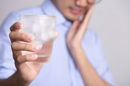 Young man with sensitive teeth and hand holding glass of cold water with ice. Healthcare concept.