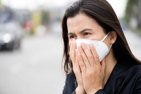 Close up of a businesswoman in a suit wearing Protective face mask and cough, get ready for Coronavirus and pm 2.5 fighting against beside road in background.