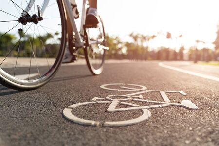 Close up cycling logo image on road with athletic women cyclist legs riding Mountain Bike in background at the morning. 版權商用圖片