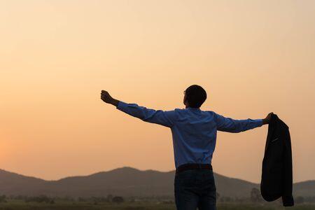 Ein glücklicher asiatischer hübscher junger Geschäftsmann, der Arme ausbreitet und seinen Anzug während des Sonnenuntergangs Sonnenaufgangberges im Hintergrund hält. Geschäftserfolgskonzept.