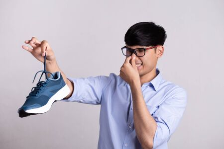 Close up asian man holding dirty stinky shoe with an expression of disgust. Healthcare concept.