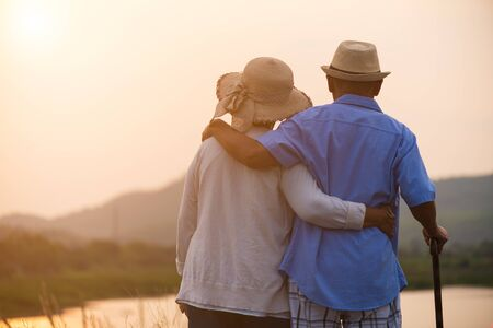 A happy senior couple asian old man and woman standing in summer near mountain and lake during sunrise or sunset . Senior healthcare and relationship concept. 版權商用圖片