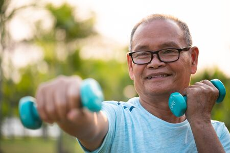Asian old man doing physical exercise outdoor with dumbbells. Be healthy and strong. Work on the muscles. Senior healthcare and sport concept. Stok Fotoğraf