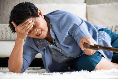 Kranke asiatische alte Frau mit Kopfschmerzen, die auf dem Boden liegt, nachdem sie zu Hause gefallen ist. Seniorengesundheitskonzept.