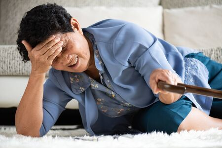 Sick asian old woman with headache lying on the floor after falling down at home. Senior healthcare concept.