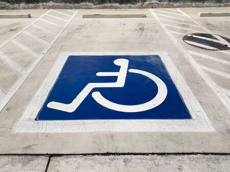 International handicapped (wheelchair) or Disabled parking symbol painted in bright blue on parking space.