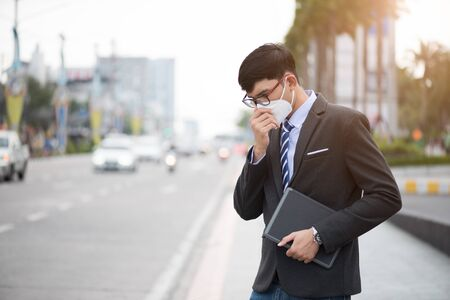 Close up of a businessman in a suit wearing Protective face mask and cough, get ready for Coronavirus and pm 2.5 fighting against in city background.