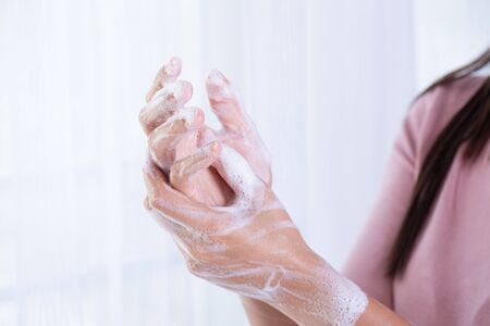 Closeup woman washing hands with soap on white background. Healthcare and disinfection concept. Stock Photo