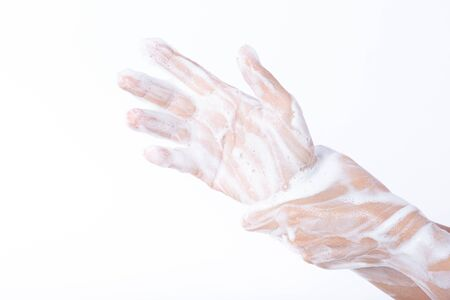 Closeup woman washing hands with soap on white background. Healthcare and disinfection concept. Standard-Bild