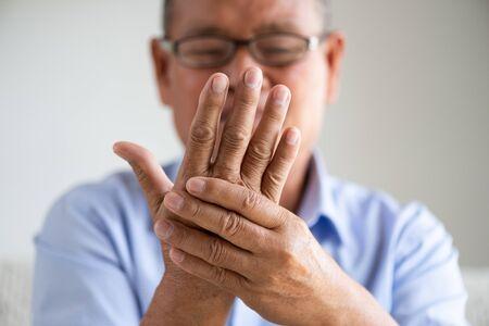 Asiatischer alter Mann, der auf dem Sofa sitzt und Handschmerzen hat, Handverletzung zu Hause. Seniorengesundheitskonzept. Standard-Bild