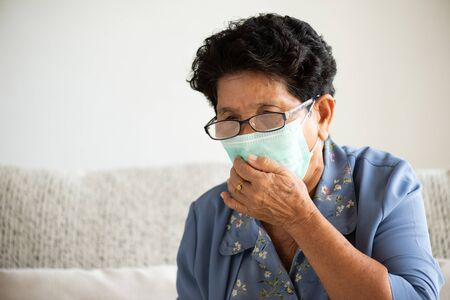Sick asian old woman wearing Protective face mask, get ready for Coronavirus and pm 2.5 fighting, sitting on sofa at home. Senior healthcare concept.