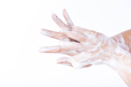 Closeup woman washing hands with soap on white background. Healthcare and disinfection concept.