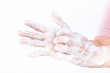 Closeup woman washing hands with soap on white background. Healthcare and disinfection concept. 写真素材