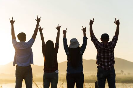 Group of happy friends are having fun with raised arms together in front of mountain and enjoy sunrise sunset showing unity and teamwork. Friendship happiness leisure partnership team concept.