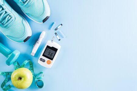 Concepto de estilo de vida, comida y deporte saludable. Vista superior del probador de diabetes con equipo de atleta; cinta métrica, mancuerna verde y fruta sobre fondo azul pastel brillante.