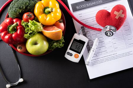 World diabetes day and healthcare concept. Patient's blood sugar control, diabetic measurement, and healthy food eating nutrition with red heart on black background.