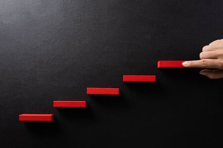 Concept of building success foundation. Women hand put red wooden block in the shape of a staircase. Success in business growth concept on black background.