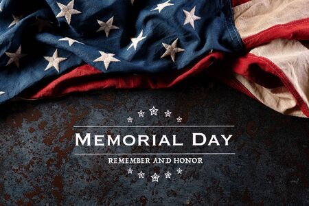 Happy Memorial Day. American flags with the text REMEMBER & HONOR against a black stone texture background. May 25. Фото со стока