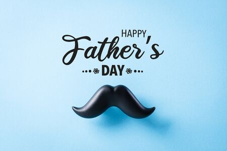 Father's day concept. Black moustache on blue paper background.