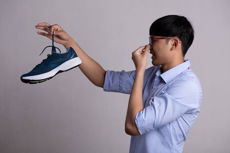 Close up asian man holding dirty stinky shoe with an expression of disgust. Healthcare concept. Foto de archivo
