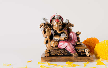 Happy Ganesh Chaturthi festival, Bronze Ganesha statue and Golden texture with flowers, Ganesh is hindu god of Success. Stock Photo