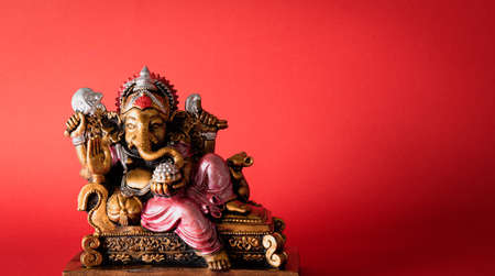 Happy Ganesh Chaturthi festival, Bronze Ganesha statue and Golden texture with flowers, Ganesh is hindu god of Success.
