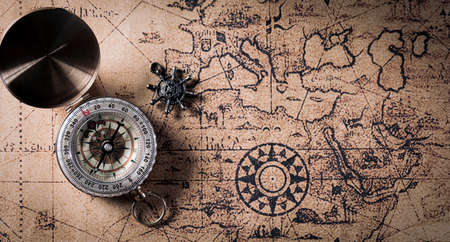 Happy Columbus Day concept. Vintage compass and retro treasure manuscript. Flat lay, top view with copy space.