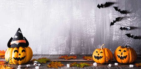 Orange ghost pumpkins with witch hat on gray wooden board background with bat. halloween concept. Zdjęcie Seryjne