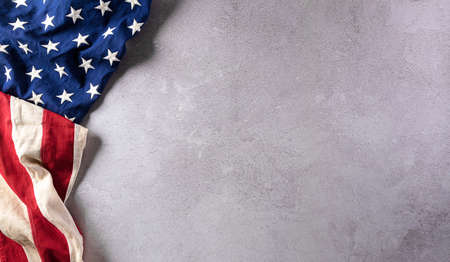 Happy Veterans Day concept. American flags against gray stone background. November 11.