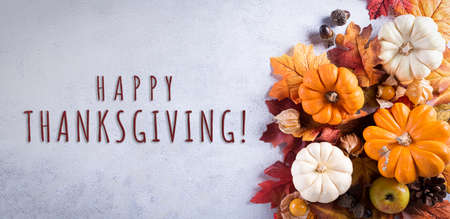 Thanksgiving background decoration from dry leaves and pumpkin on gray stone background. Flat lay, top view with Happy Thanksgivings text.
