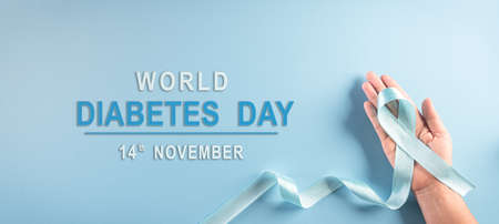 World diabetes day awareness concept. Hand holding blue ribbon, symbolic bow color raising awareness in diabetes day on pastel background,  14 November.
