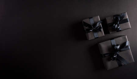 Top view of black Christmas gift boxes with black ribbon on black  background with copy space for text. Black Friday composition.