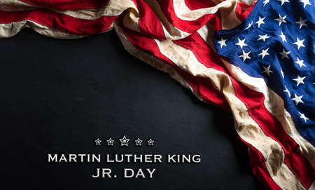 Martin Luther King Day anniversary concept. American flag against black wooden background Фото со стока