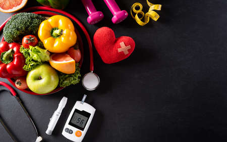 World health day and medical concept. Top view of healthy food in plate with stethoscope, red heart for cholesterol diet and diabetes control set on dark background.