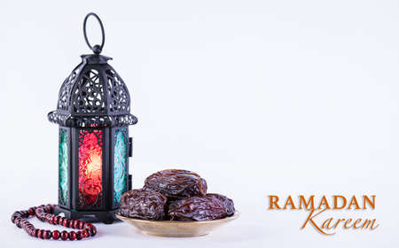 Ramadan food and drinks concept. Ramadan arabian lamp, wood rosary, and dates fruit on white background. Zdjęcie Seryjne