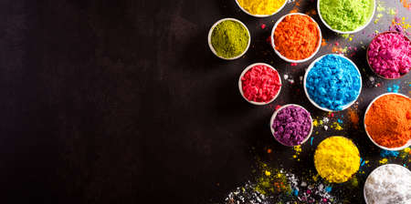Happy holi festival decoration.Top view of colorful holi powder on dark background.