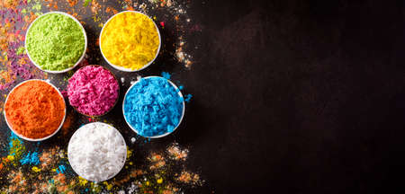 Happy holi festival decoration.Top view of colorful holi powder on dark background with copy space for text.