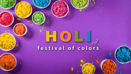 Happy holi festival decoration.Top view of colorful holi powder on purple  background with  text.