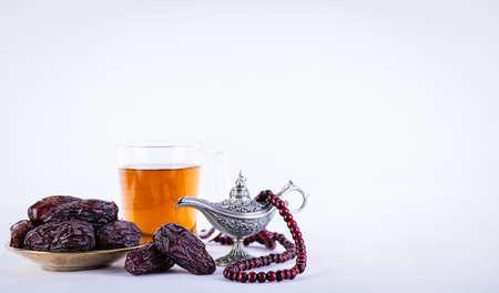 Ramadan food and drinks concept. Ramadan arabian lamp, wood rosary, tea, and dates fruit on white background. Zdjęcie Seryjne - 166246850