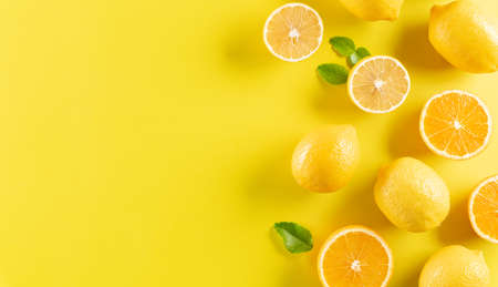Summer composition made from oranges, lemon and green leaves on pastel yellow background. Fruit minimal concept. Zdjęcie Seryjne