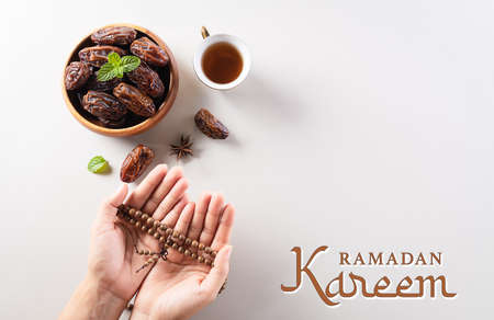 Table top view image of decoration Ramadan Kareem background,  dates fruit, coffee and hand with rosary beads.