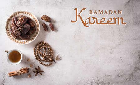 Ramadan food and drinks concept. Ramadan wood rosary, tea, and dates fruits on dark stone background. Zdjęcie Seryjne