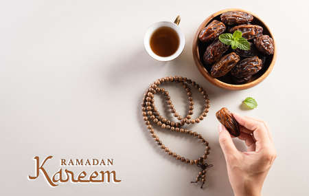 Ramadan Kareem background concept,  Hands picking up dates fruit, tea and rosary beads. Flat lay background with Ramadan text.
