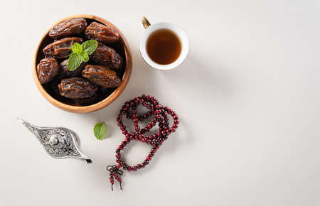 Table top view image of decoration Ramadan Kareem,  dates fruit, aladdin lamp and rosary beads on gray  background. Flat lay with copy space.