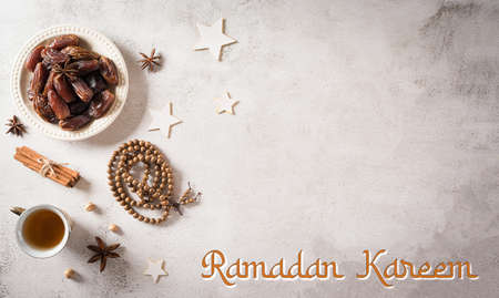 Ramadan food and drinks concept. Ramadan arabian lamp, wood rosary, tea, and dates fruit on dark stone background with text.