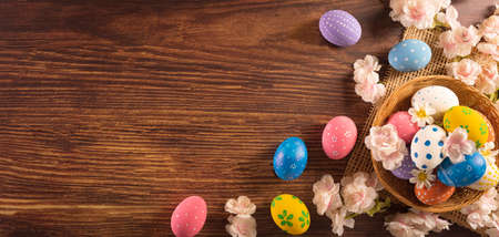 Happy easter! Colourful of Easter eggs in the nest with flower on dark wooden background. Greetings and presents for Easter Day celebrate time. Flat lay ,top view. Zdjęcie Seryjne